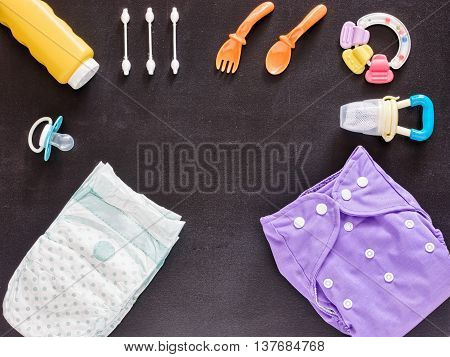 Baby set of cloth diaper, disposable diaper, baby powder, tither, cotton buds, spoons, soother and nibbler on dark background with copy space. Top view or flat lay