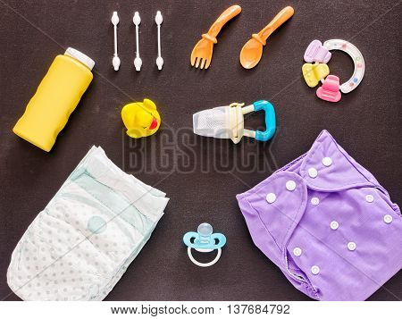 Baby set of cloth diaper, disposable diaper, baby powder, tither, cotton buds, spoons, soother, nibbler and rubber duckling on dark background. Top view or flat lay
