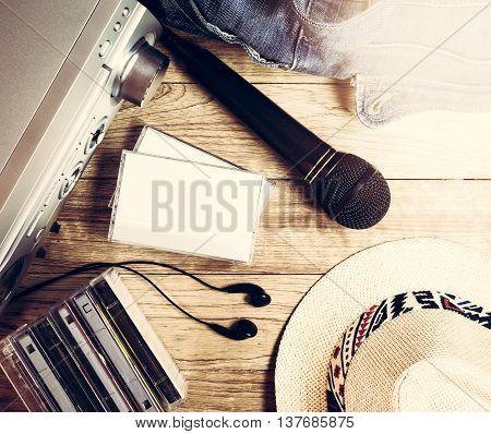Set of audio device microphone earphones cassette denim handbag and hat on wooden vintage background
