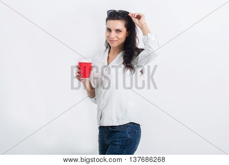Beautiful young woman posing in jeans on a white wall with a takeaway coffee.