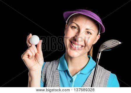 Happy golf player posing with a golf club and golf ball on black background