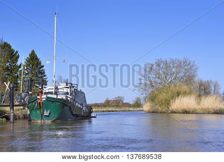 Sunny riverside with marshland and reeds. View from a boat to a river with little pier or jetty in springtime.