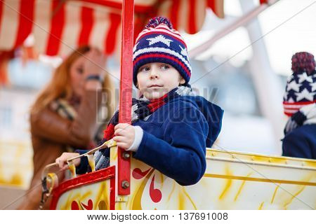 Adorable little kid boy on a carousel, ferris wheel at Christmas funfair or market. Mother and sibling on background. Happy child having fun.