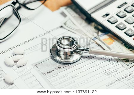Cost of health care concept stethoscope and calculator on table