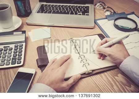Image of business hands with pen over business document in working environment