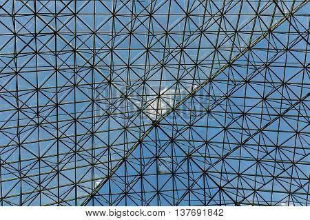 Glass Atrium Ceiling with Metal Grid under blue sky