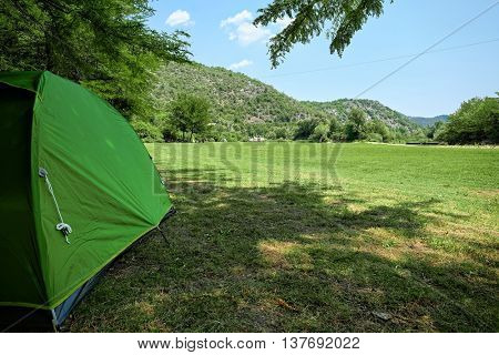 Skadar Park camping with green tent on back yard field, Montenegro