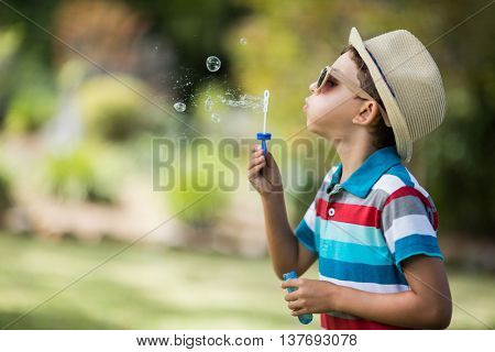 Cute young boy in sunglasses blowing bubbles through bubble wand in park