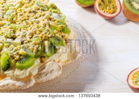 Meringue Pavlova with whipped cream and fresh kiwi and passion fruit selective focus.