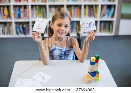 Disabled girl holding placard that reads I Can in library at school