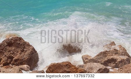 Sea ​​water splashes on the rock, close up.Scenic view of waves breaking against rock on summer day. Vintage toned image