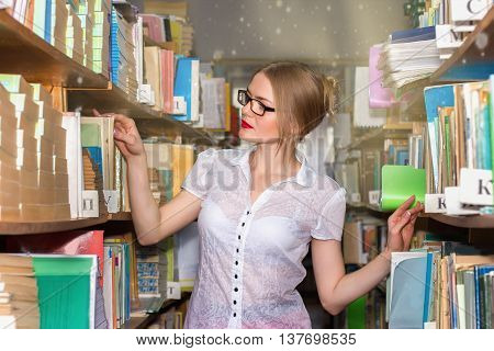 Girl In The Library Between Racks With Books, A Beautiful Blonde With Glasses Gets Knowledge And Edu