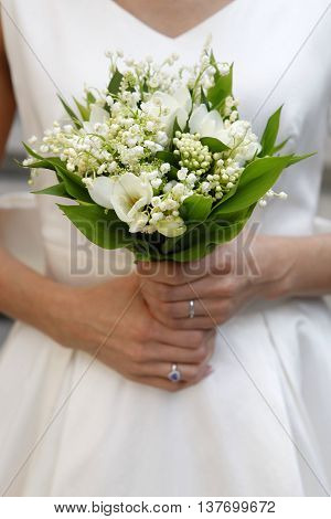The bride holds a wedding bouquet close-up