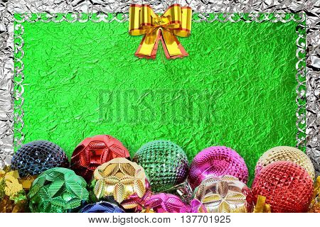 Christmas background with christmas ball and pattern on the green foil background