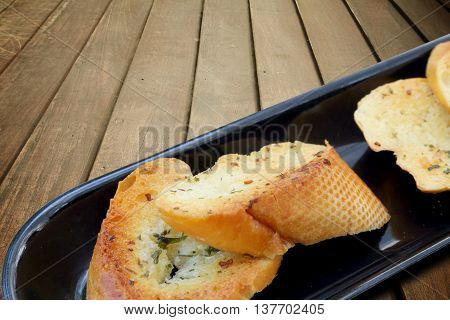 Close-up of a dish of garlic bread on wooden deck table