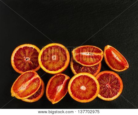 Sliced Sicilian red oranges on black stone background. Top view.