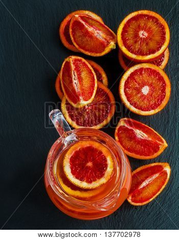 Sliced Sicilian red oranges and orange juice in glass jug on black stone background. Top view.