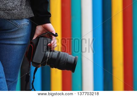 photographer holding camera close-up. Back view Selective focus. colored vertical stripes in the background.