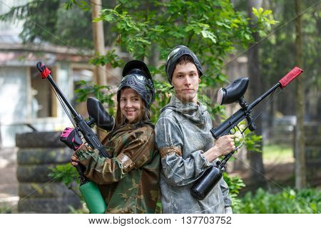 Happy couple posing with paintball guns outdoors