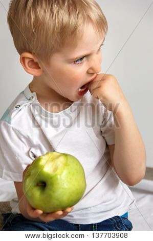 Little boy touching the hands of the teeth that are going out baby tooth eating apple green on a white background soft focus