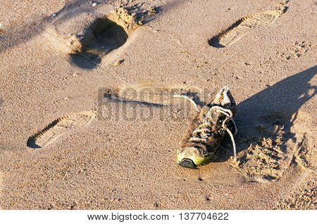 Old Abandoned Wet Dirty Shoe On Beach Sand
