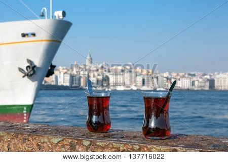 Turkish Tea glassy cups located on seafront harbor parapet river and urban landscape con background