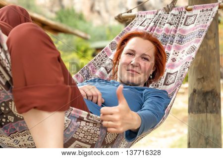 Woman lying in Hammock at Patio of Wooden Rural Cottage making OK hand Gesture Smiling and Positive green Garden on background