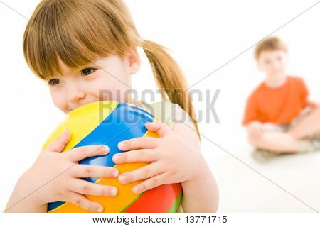 Photo of little girl holding colorful ball in hands with her brother at the background