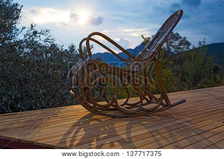 Vintage wooden Rocking Chair at lumber Cottage Terrace Patio Forest and Mountains Sunrise