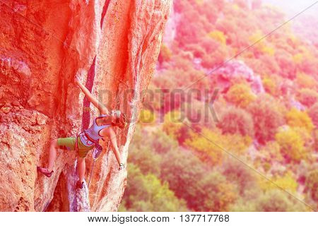 Smiling Young cute Female Climber Hanging on one hand on rocky Wall over colorful forest with backlight shining Sun