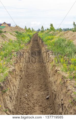 A trench in the ground for laying of water supply system in residential area
