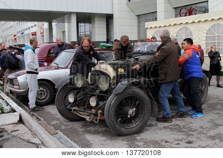 PERM RUSSIA - JUNE 29 2016: Rally of retro-cars Peking-Paris 2016 June 29 2016 in Perm Russia. The participants of the rally parked car near Bentley hotel.