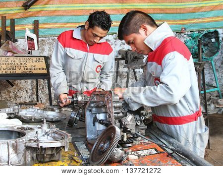 Magdalena Cajamarca Peru - July 8 2016: Two student mechanics work on auto parts in shop in Magdalena Cajamarca Peru on July 8 2016