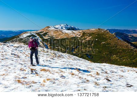 Female Hiker with Backpack walking up on Snow Slope Mountains View blue Sky sunny Day