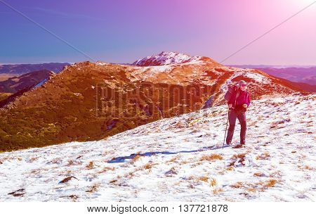 Female Hiker with Backpack walking up on Snow Slope Mountains View blue Sky Sun shining