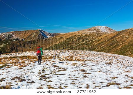 Hiker Man with Backpack walking on Snow Slope Trail Mountains View blue Sky sunny Day Bright sporty Clothing red Jacket