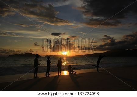 people are having fun on the beach at the sunset