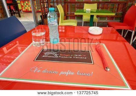 ALBA IULIA, ROMANIA - AUGUST 12, 2015: modern colorful table set with romanian text 'va dorim pofta buna' that is 'enjoy your meal'