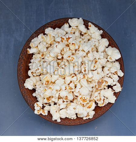 A bowl of popcorn on a bowl of popcorn on a blue background background. top view
