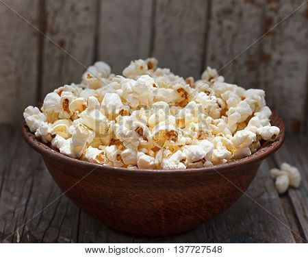 Fresh popcorn in bowl on white wooden table. Selective focus.