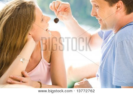 Image of man in t-shirt feeding the beautiful woman