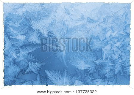 Bright blue frost pattern on a window glass in a white frame (as an abstract winter background) retro style