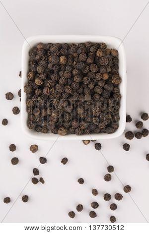 Black pepper corns scattered on white background and Black pepper isolated on white background.