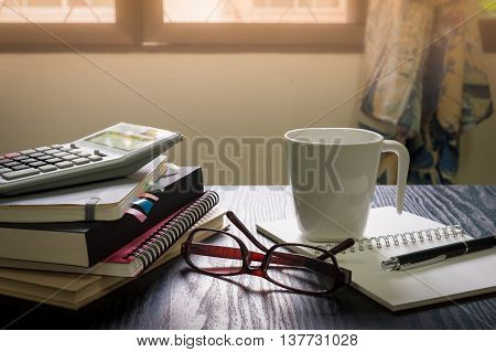 Coffee cup put down on table beside notebooks glasses and pen in morning time on work day. Freelance business working concept