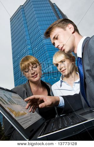 Image of friendly business group looking at laptop screen while man pointing at it
