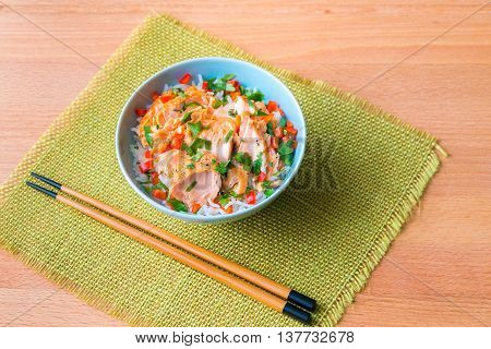 Bowl of rice with poached salmon and vegetables.