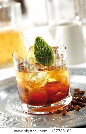 Coffee and ginger cocktail prepared with espresso coffee ginger and rum. Garnished with mint leaves.