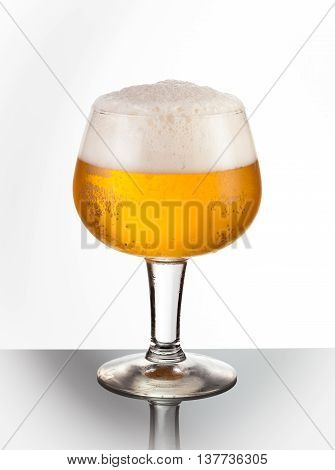 An ice cold snifter glass of refreshing draft beer