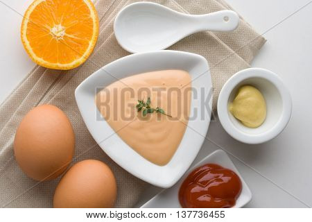 Cocktail sauce in a white bowl with orange eggs ketchup and mustard. Salad and seafood dressing.