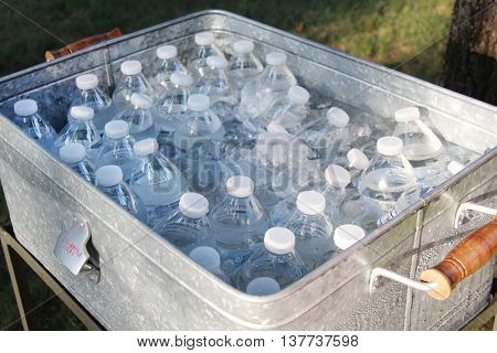 Bottles with water in a large cart filled with ice